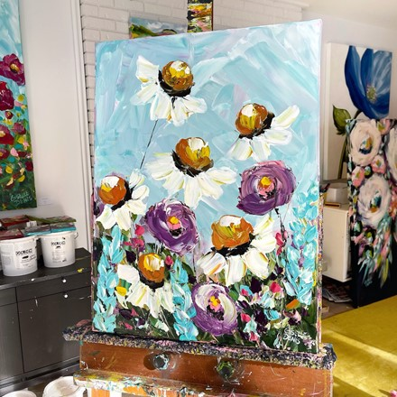 Painting by Giselle Denis Canadian fine artist of white daisies with purple wildflowers on a blue sky background.