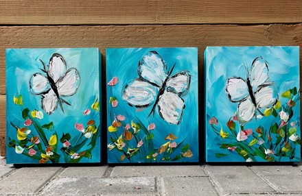 Painting by Giselle Denis Canadian fine artist of white butterflies on a blue background with flowers in the foreground.