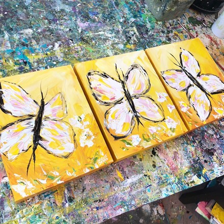 Painting by Giselle Denis Canadian fine artist of white butterflies on a yellow background with flowers.
