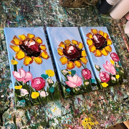 Painting by Giselle Denis Canadian fine artist of sunflowers with pink, yellow and blue wildflowers under a blue sky background.