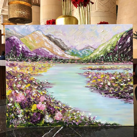 Painting by Giselle Denis Canadian fine artist of colourful mountains on a lake with wildflowers in the foreground.