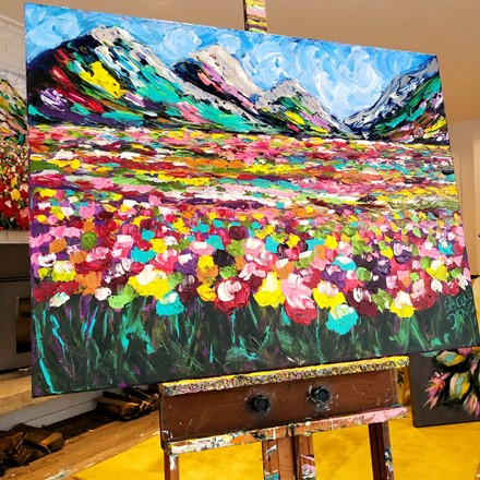 Painting by Giselle Denis Canadian fine artist of colourful mountains with windflowers in the foreground under a blue sky.