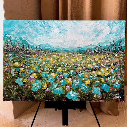 Painting by Giselle Denis Canadian fine artist of a field of wildflowers under a blue sky with trees in the background.